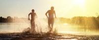 Glckliche junge Menschen laufen und springen am See beim Sonnenuntergang